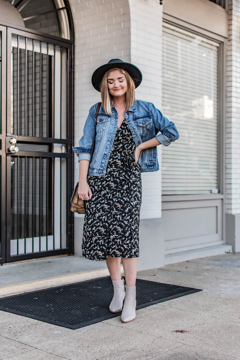 Two ways to were a wrap dress this fall. Wearing a black floral midi wrap dress from wearNYLA. Dressed down with a denim jacket and boots.