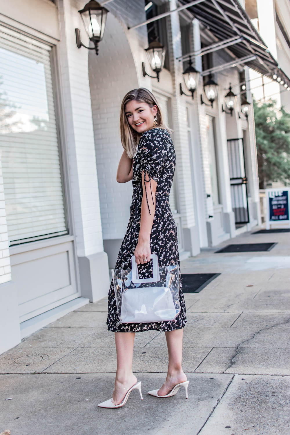 Two ways to were a wrap dress this fall. Wearing a black floral midi wrap dress from wearNYLA.